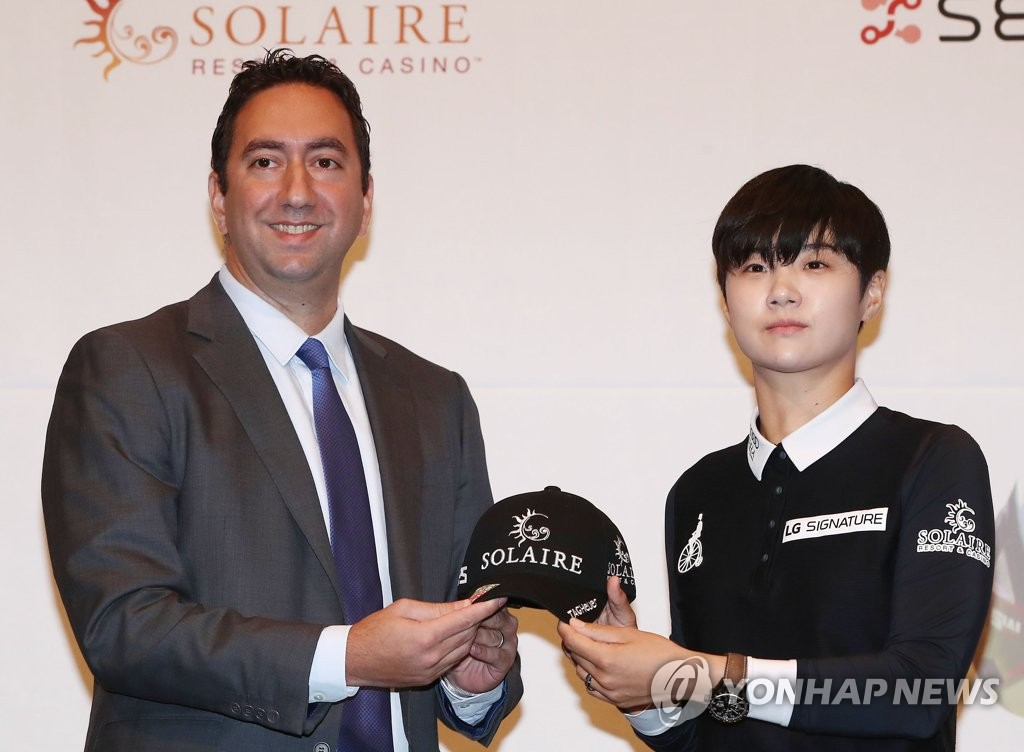 Cyrus Sherafat (L), executive vice president for casino marketing at Solaire Resort & Casino, and South Korean LPGA golfer Park Sung-hyun hold Park's new hat bearing Solaire's logo during her corporate sponsorship signing ceremony in Seoul on Feb. 14, 2019. (Yonhap)