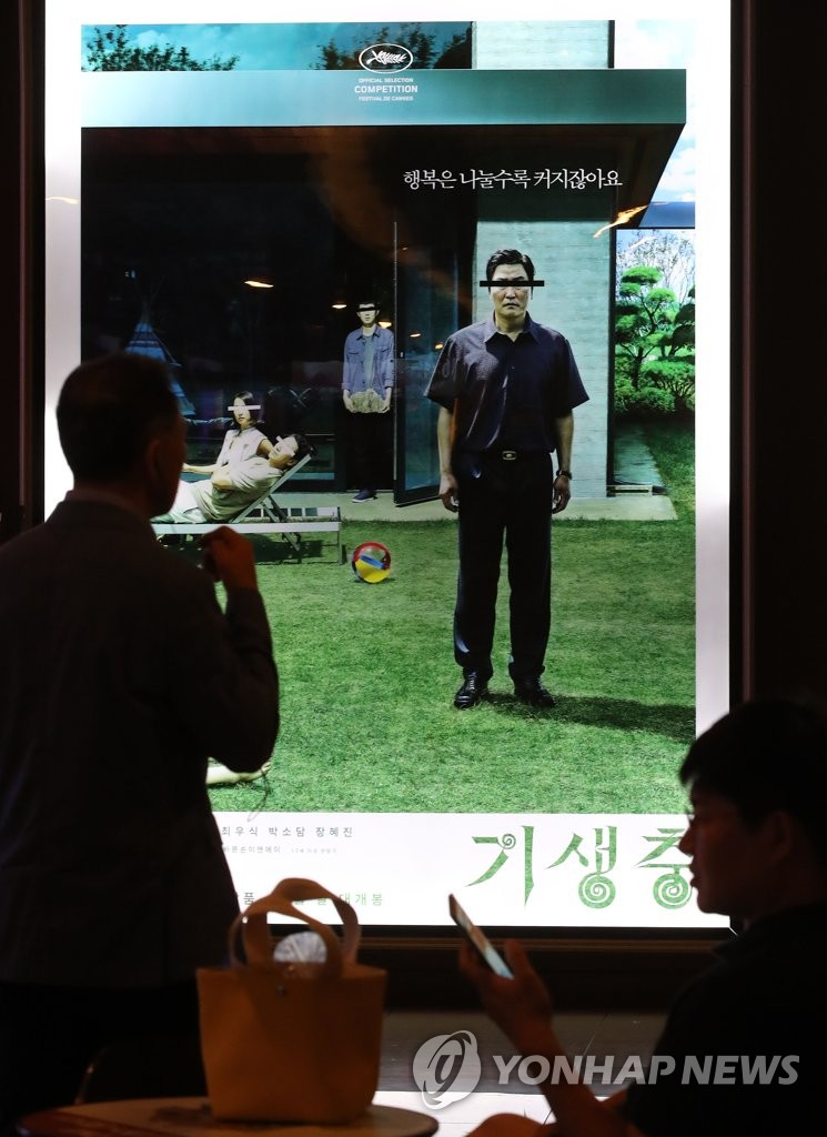 "Citizens pass by a poster for the Palme d'Or-winning film ""Parasite"" at a Seoul theater on May 30, 2019, its opening day in South Korea. (Yonhap)"