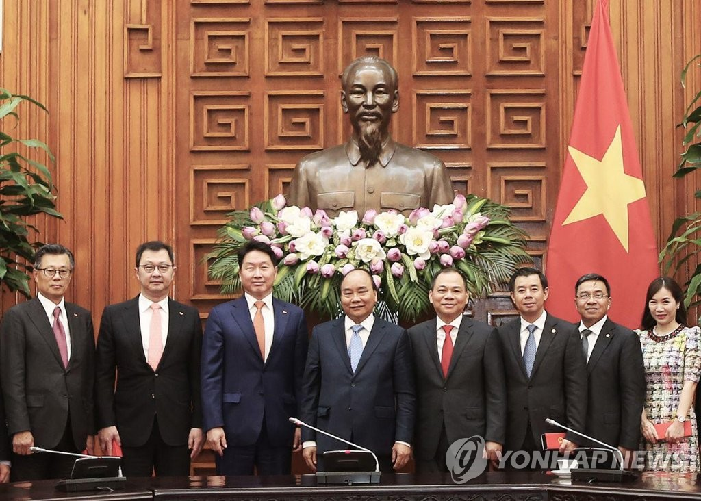 This photo provided by SK Group shows SK Group Chairman Chey Tae-won (3rd from L) and Vietnamese Prime Minister Nguyen Xuan Phuc (4th from L) with other officials at Vietnam's prime minister's office in Hanoi on June 5, 2019. (PHOTO NOT FOR SALE) (Yonhap)