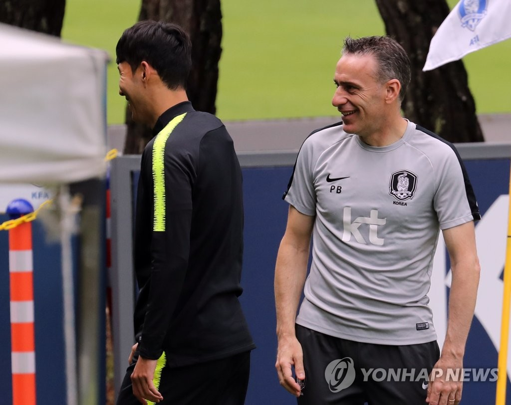 South Korea men's football head coach Paulo Bento (R) shares a laugh with his captain, Son Heung-min, before the start of practice at the National Football Center in Paju, Gyeonggi Province, on June 10, 2019. (Yonhap)
