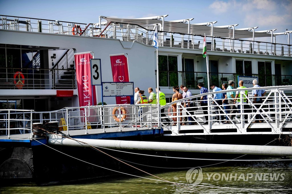 This AFP photo taken on June 10, 2019, shows Hungarian police and experts in Budapest boarding the Viking Sigyn, the cruise ship that hit the sightseeing boat carrying South Korean tourists, to carry out an additional search as part of a probe into the deadly sinking. (PHOTO NOT FOR SALE) (Yonhap)