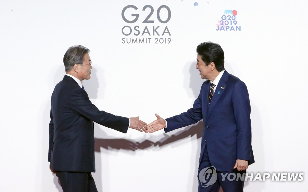 This photo, taken June 28, 2019, shows South Korean President Moon Jae-in (L) shaking hands with Japanese Prime Minister Shinzo Abe during the Group of 20 summit in Osaka, Japan. (Yonhap)