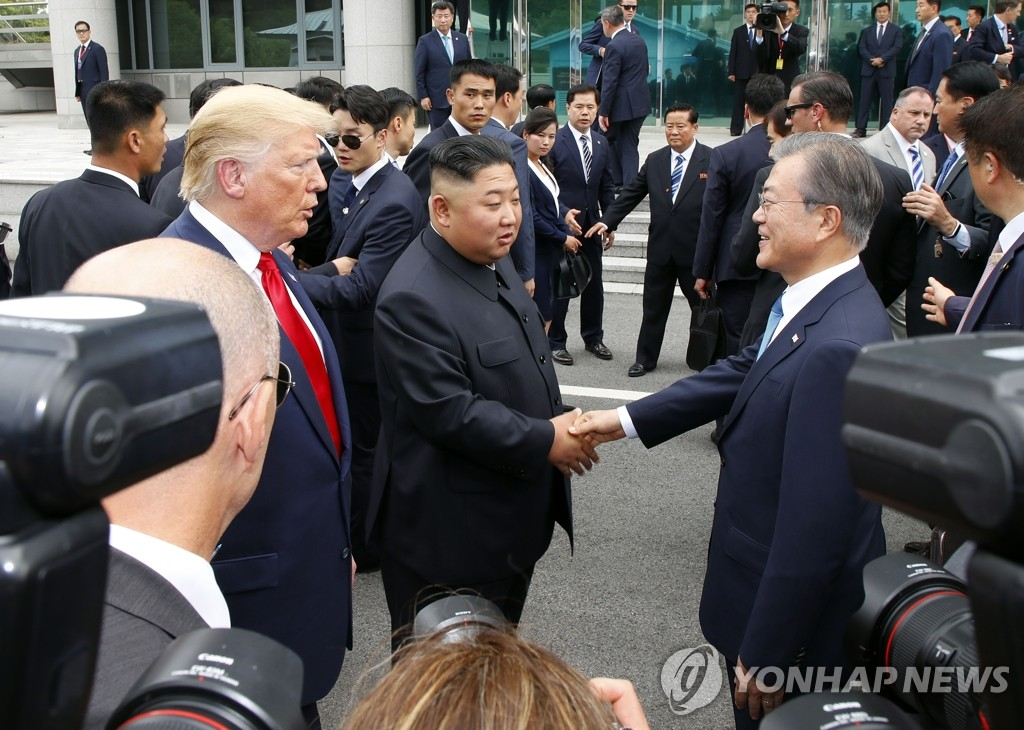In this file photo, taken on June 30, 2019, South Korean President Moon Jae-in (R) meets with North Korean leader Kim Jong-un, alongside U.S. President Donald Trump (L), at the truce village of Panmunjom in the Demilitarized Zone, which separates the two Koreas. (Yonhap)