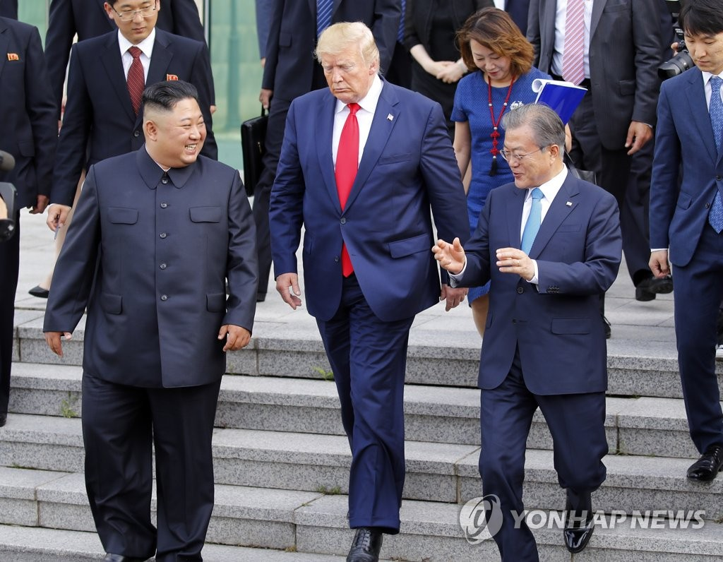 In the file photo taken June 30, 2019, North Korean leader Kim Jong-un (L) walks with U.S. President Donald Trump (C) and South Korean President Moon Jae-in toward the northern side of the truce village of Panmunjom in the Demilitarized Zone, which separates the two Koreas, after holding talks with Trump at the Freedom House on the village's southern side. (Yonhap)