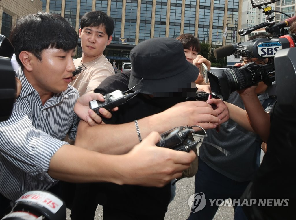 A South Korean man (C) suspected of assaulting a Japanese woman is surrounded by reporters after being investigated by police at Mapo Police Station in Seoul on Aug. 24, 2019. (Yonhap)