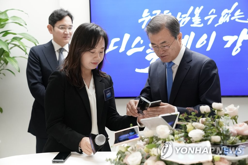 President Moon Jae-in tries out a product that uses next-generation display technology during his visit to Samsung Display's factory in Asan, South Chungcheong Province, on Oct. 10, 2019. (Yonhap)