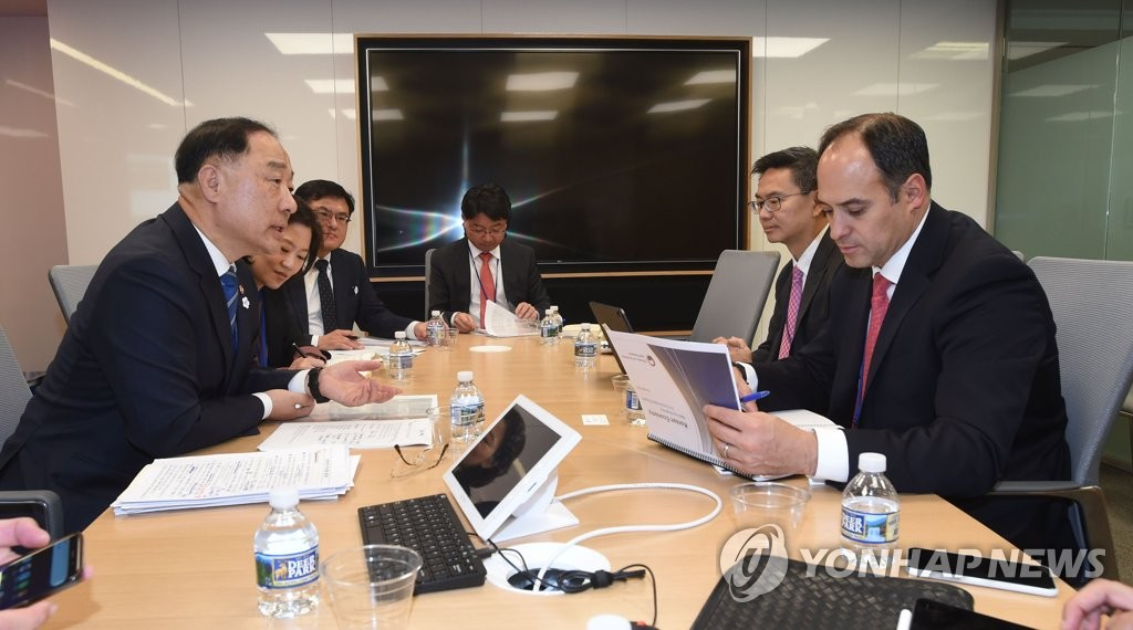 In this photo provided by South Korea's finance ministry, Finance Minister Hong Nam-ki meets with an S&P representative during his visit to the International Monetary Fund in Washington on Oct. 17, 2019. (PHOTO NOT FOR SALE) (Yonhap)