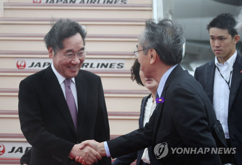 South Korean Prime Minister Lee Nak-yon (L) shakes hands with Japanese officials at Haneda Airport in Tokyo on Oct. 22, 2019, on his arrival in Tokyo for a three-day trip to attend the Japanese emperor's enthronement ceremony. (Yonhap)