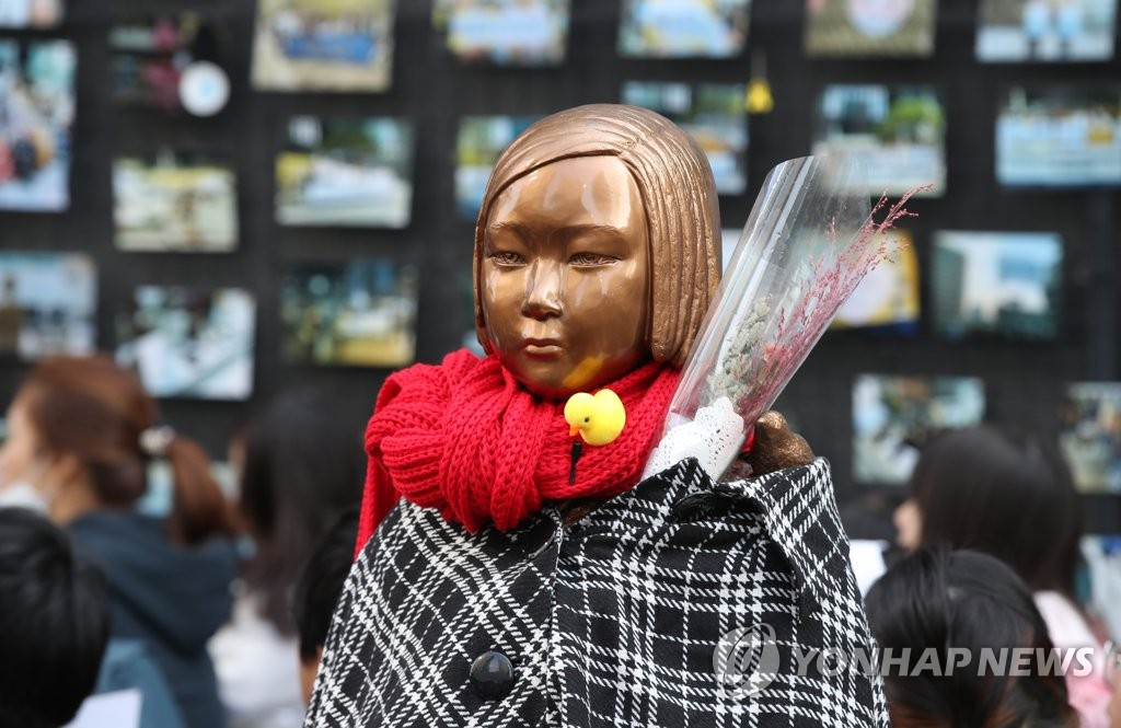 A statue of a girl symbolizing Korean victims of Japan's wartime sexual enslavement, installed in front of the Japanese Embassy's former compound in central Seoul, is seen wearing a red scarf and covered in a blanket on Nov. 6, 2019. (Yonhap)