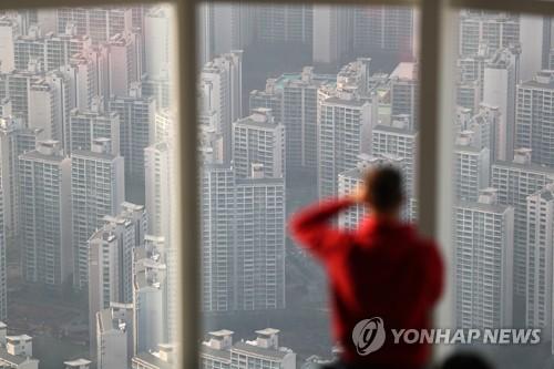 서울 송파구 잠실 롯데월드타워를 찾은 시민이 인근 아파트 단지를 바라보고 있다. [연합뉴스 자료사진]
