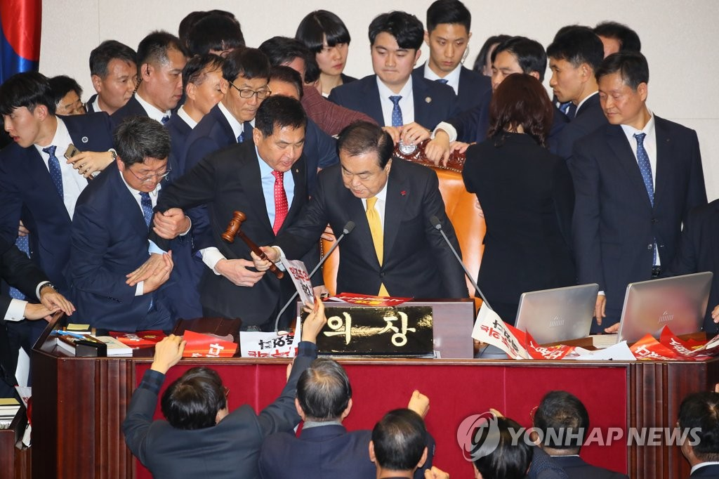 National Assembly Speaker Moon Hee-sang (C) bangs the gavel to announce the passage of an electoral reform bill amid protests by Liberty Korea Party lawmakers at the National Assembly on Dec. 27, 2019. (Yonhap)