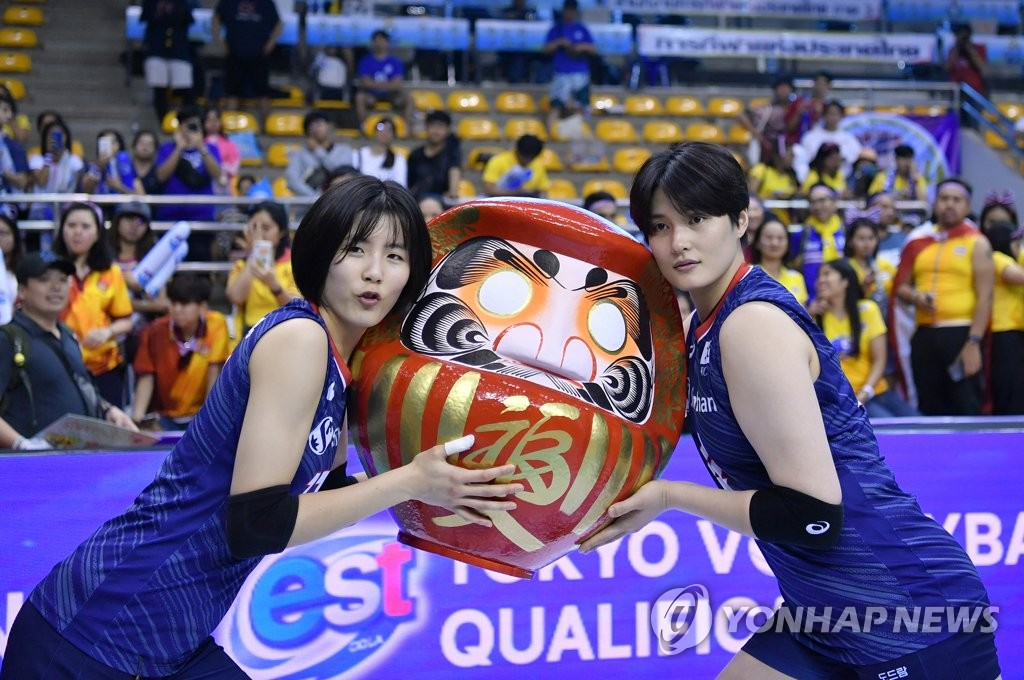 In this photo provided by FIVB on Jan. 12, 2020, South Korean players Lee Jae-yeong (L) and Kim Hee-jin hold the champions' trophy after beating Thailand in the final of the Asian Olympic women's volleyball qualification tournament at Korat Chatchai Hall in Nakhon Ratchasima, Thailand. (PHOTO NOT FOR SALE) (Yonhap)
