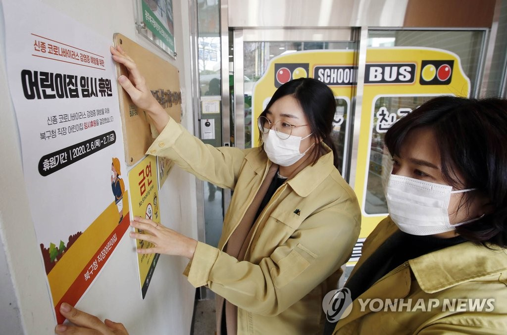 This photo provided by the Buk Ward office in Gwangju, 330 kilometers south of Seoul, shows city employees placing a temporary closure notice on the entrance of a day care center on Feb. 6, 2020. (PHOTO NOT FOR SALE) (Yonhap)