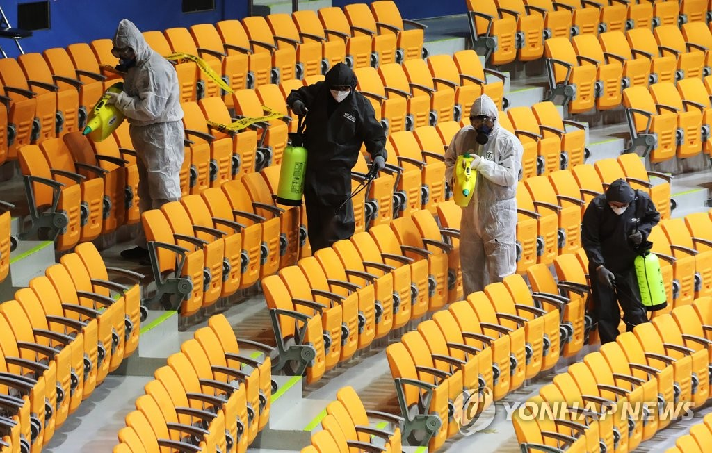 South Korea's health authorities disinfect seats at a gymnasium in Suwon, south of Seoul, to prevent the spread of the novel coronavirus on Feb. 13, 2020. (Yonhap)