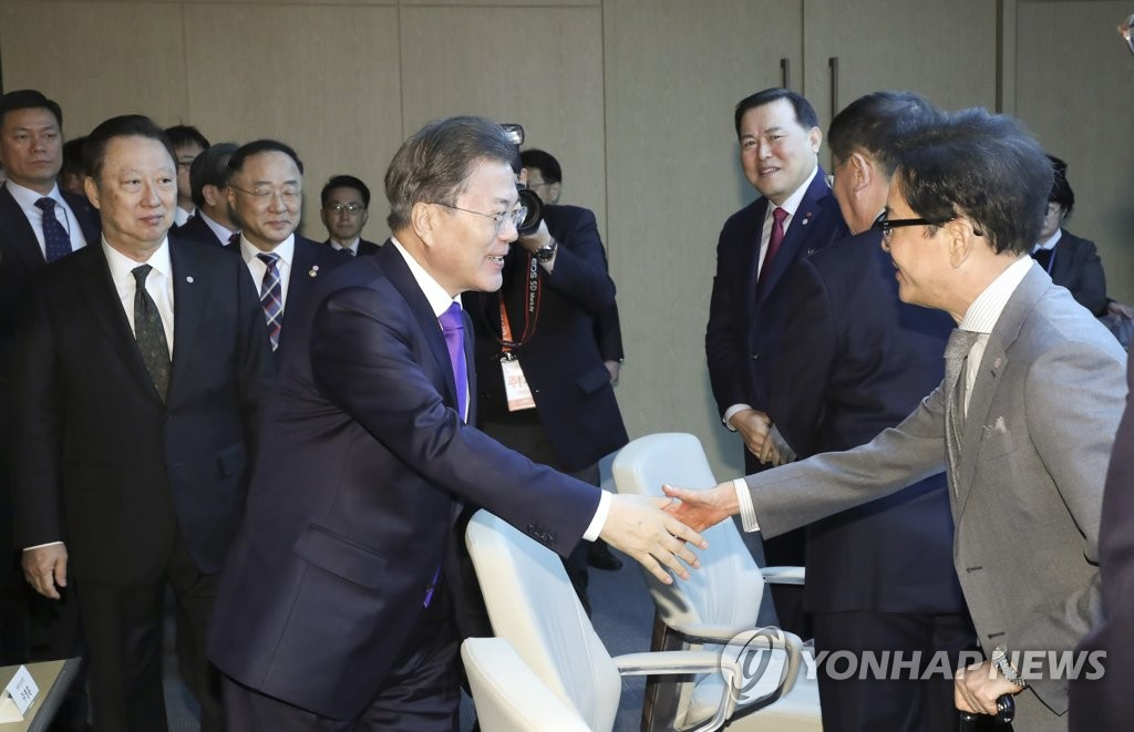President Moon Jae-in (front, L) shakes hands with CJ Group Chairman Lee Jae-hyun (front, R) at the Korea Chamber of Commerce and Industry (KCCI) in Seoul on Feb. 13, 2020. (Yonhap)