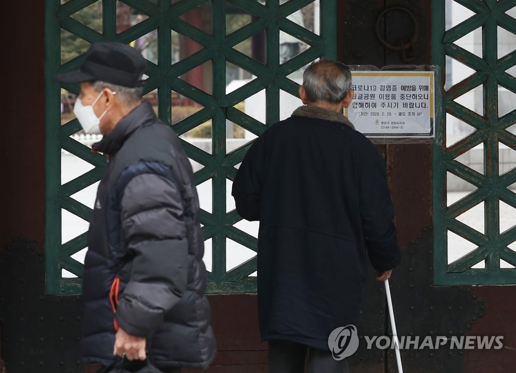 Visitors stand in front of a gate at Tapgol Park in central Seoul Feb. 21, 2020. The park, popular among the city's senior citizens, was closed down following the coronavirus outbreak in the capital. (Yonhap)