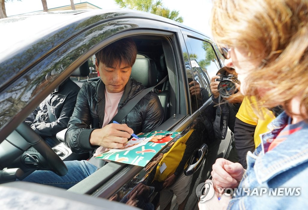 St. Louis Cardinals' pitcher Kim Kwang-hyun signs an autograph for a fan as he exits Roger Dean Chevrolet Stadium in Jupiter, Florida, on Feb. 22, 2020. (Yonhap)