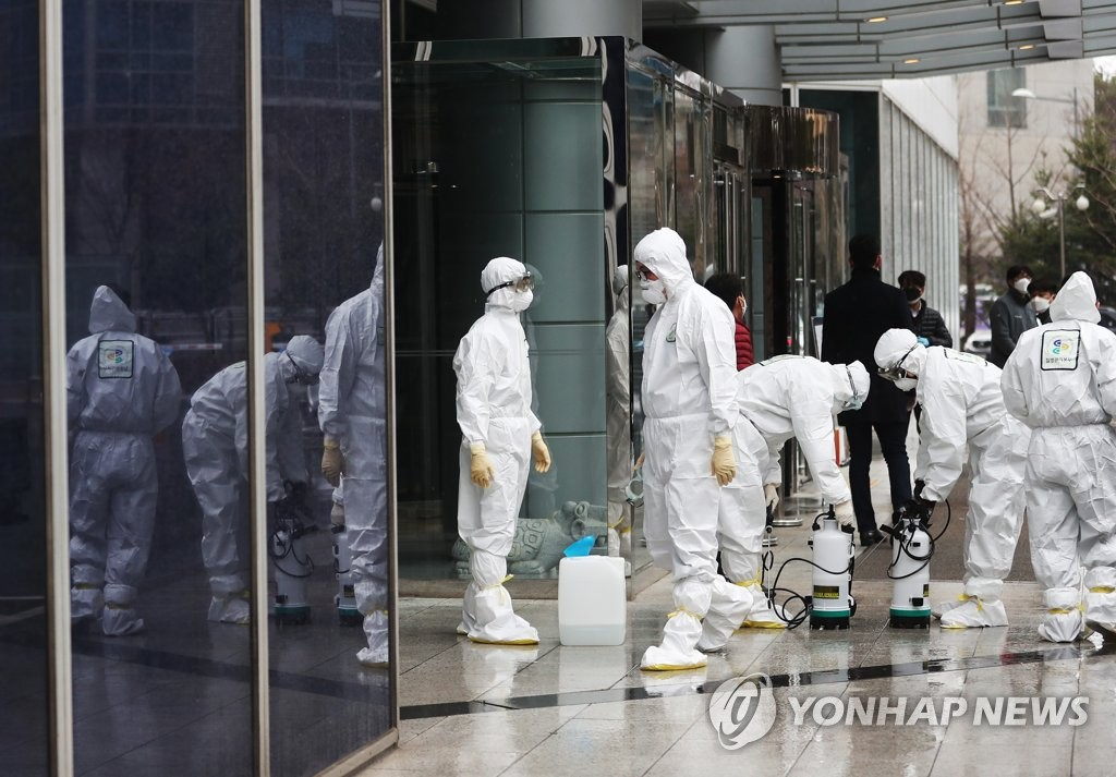 Workers clad in protective gear sort out equipment for disinfection at the LS Yongsan Tower in Seoul on Feb. 25, 2020. They disinfected the closed high-rise after a worker there was found to be infected with the new coronavirus the previous day. (Yonhap)