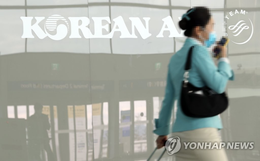 This photo taken on Feb. 25, 2020 shows a flight attendant passing by Korean Air's company logo at the No. 2 terminal of the Incheon International Airport in Incheon, just west of Seoul. (Yonhap)