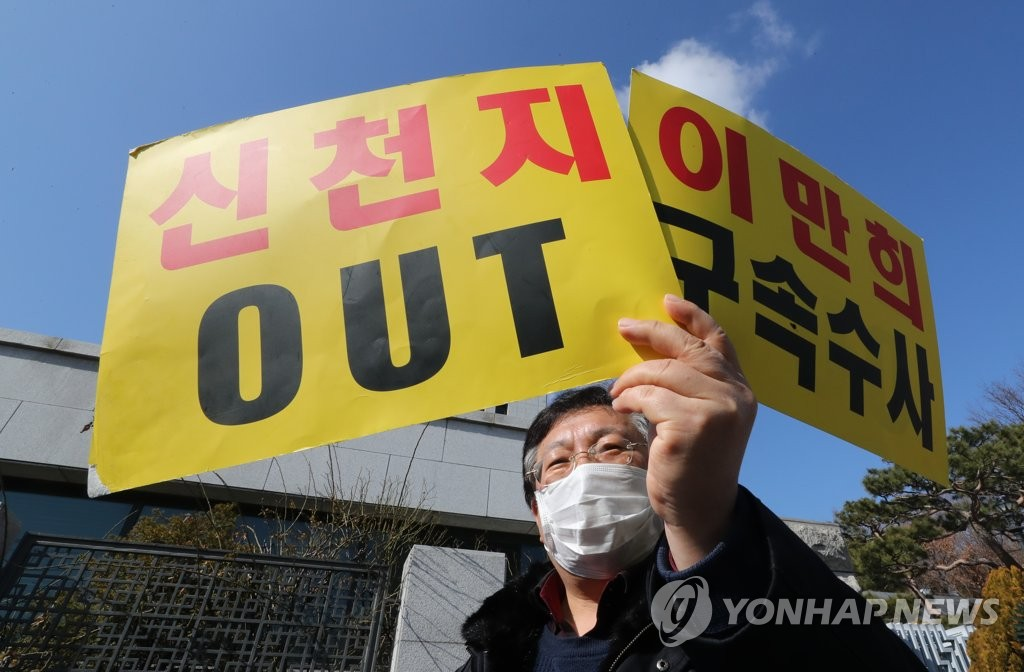 A member of a group that represents Shincheonji victims holds signs opposing the fringe religious sect at a rally in front of the Supreme Prosecutors Office on Feb. 27, 2020. (Yonhap)