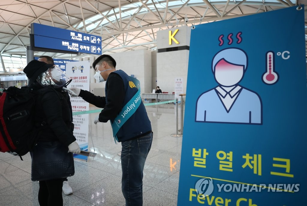 This photo taken on March 5, 2020, shows an official from the Incheon International Airport Corp. checking the temperature of a passenger at the Incheon airport in Incheon, west of Seoul. (Yonhap)
