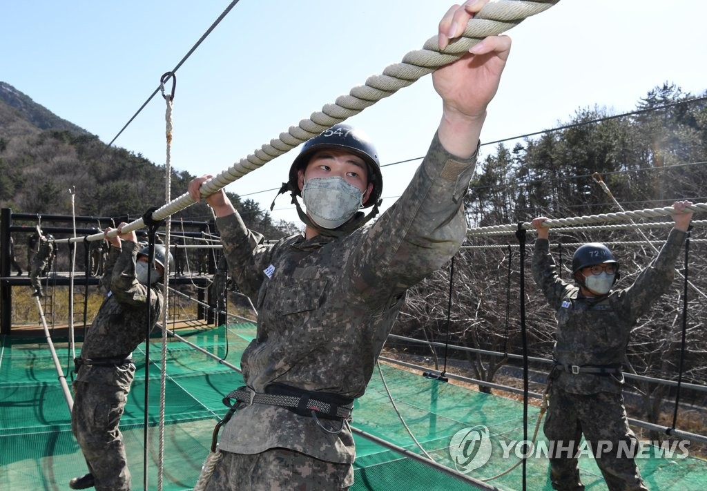In this file photo taken in March 2020 and provided by the Navy, recruits undergo combat training while wearing masks at a boot camp of the Naval Education and Training Command in the southeastern city of Changwon amid the nationwide spread of the coronavirus. (PHOTO NOT FOR SALE) (Yonhap)