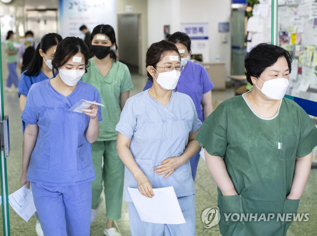 Nurses at Dongsan Hospital in virus-hit Daegu are in a line to put on protective gear before their shift on March 16, 2020. (Yonhap)