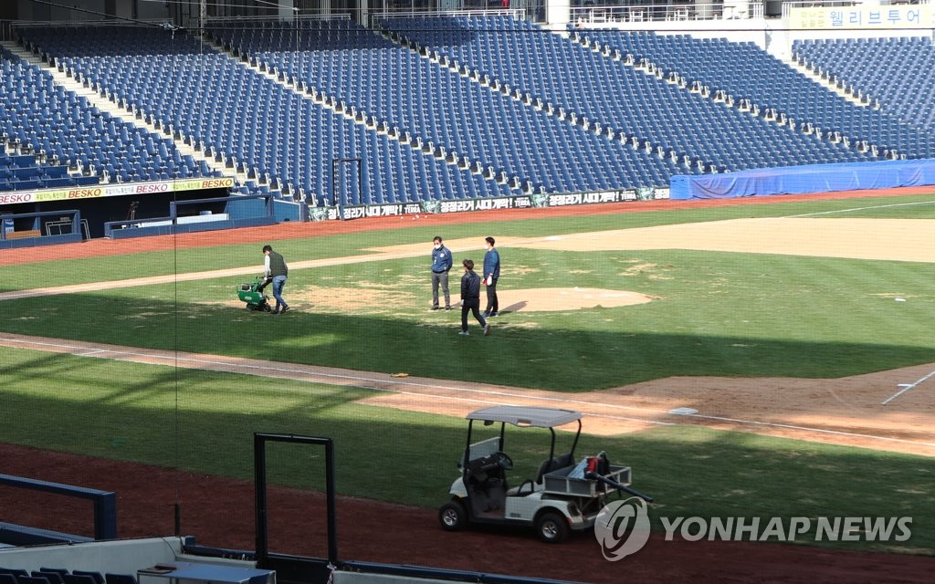 In this file photo from March 30, 2020, members of the NC Dinos' grounds crew work on the infield grass at Changwon NC Park in Changwon, 400 kilometers southeast of Seoul. (Yonhap)
