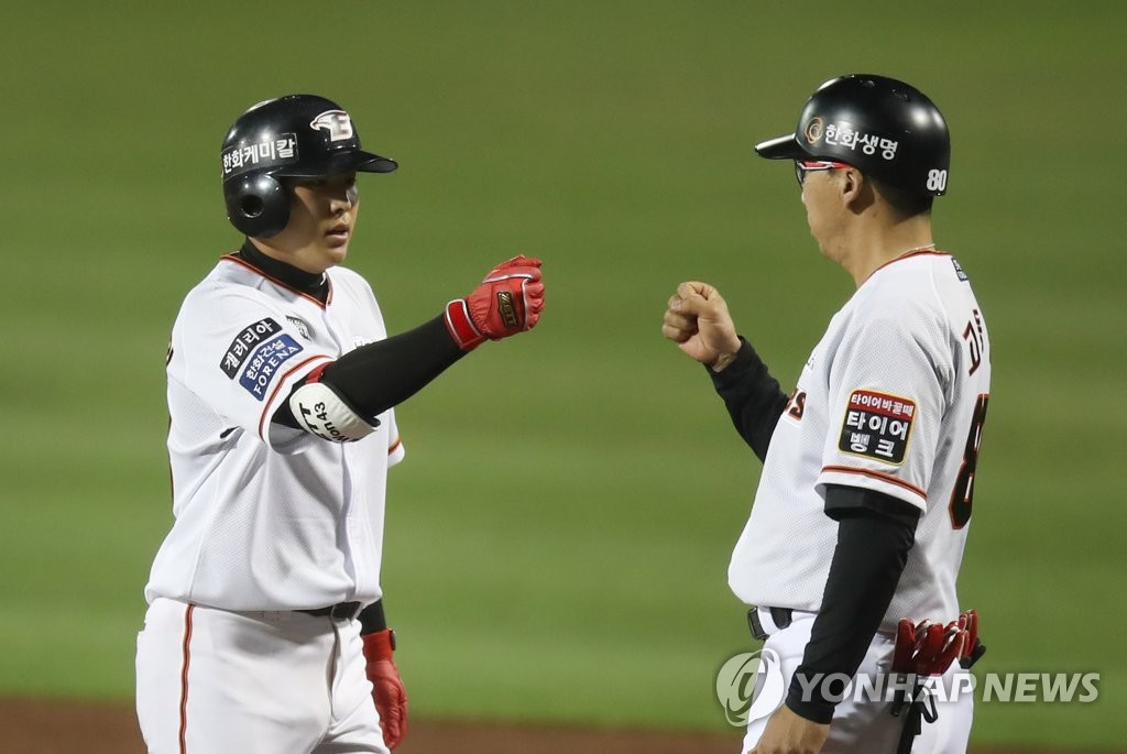 Jung Eun-won of the Hanwha Eagles (L) bumps fists with his first base coach Ko Dong-jin after a single during an intrasquad game at Hanwha Life Eagles Park in Daejeon, 160 kilometers south of Seoul, on April 16, 2020. (Yonhap)