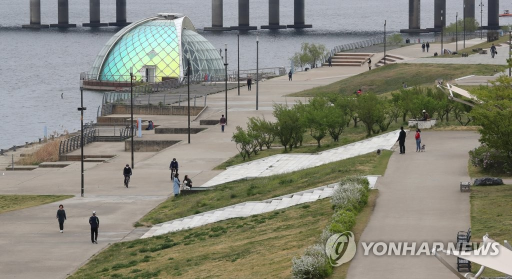 People stroll along the Han River in Seoul's western Yeouido amid the strong, government-led social distancing campaign in place on April 19, 2020. (Yonhap)