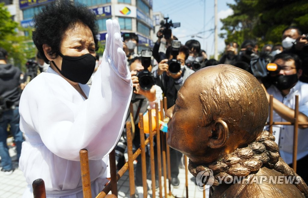 A bereaved family member slaps a statue of former President Chun Doo-hwan in front of a district court in the southwestern city of Gwangju on April 27, 2020, as Chun appeared at a trial over charges that he, in a recent memoir, defamed a deceased priest over his eyewitness account of the brutal crackdown on a 1980 pro-democracy uprising. (Yonhap)