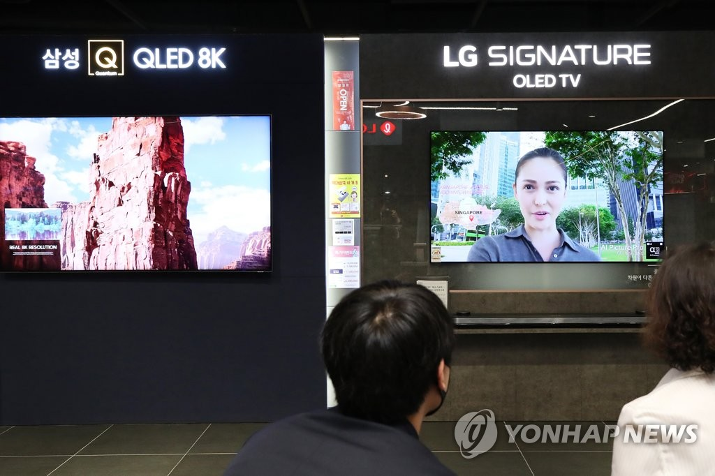 This photo, taken April 29, 2020, shows Samsung Electronics Co.'s QLED TV (L) and LG Electronics Inc.'s OLED TV displayed at a store in Seoul. (Yonhap)