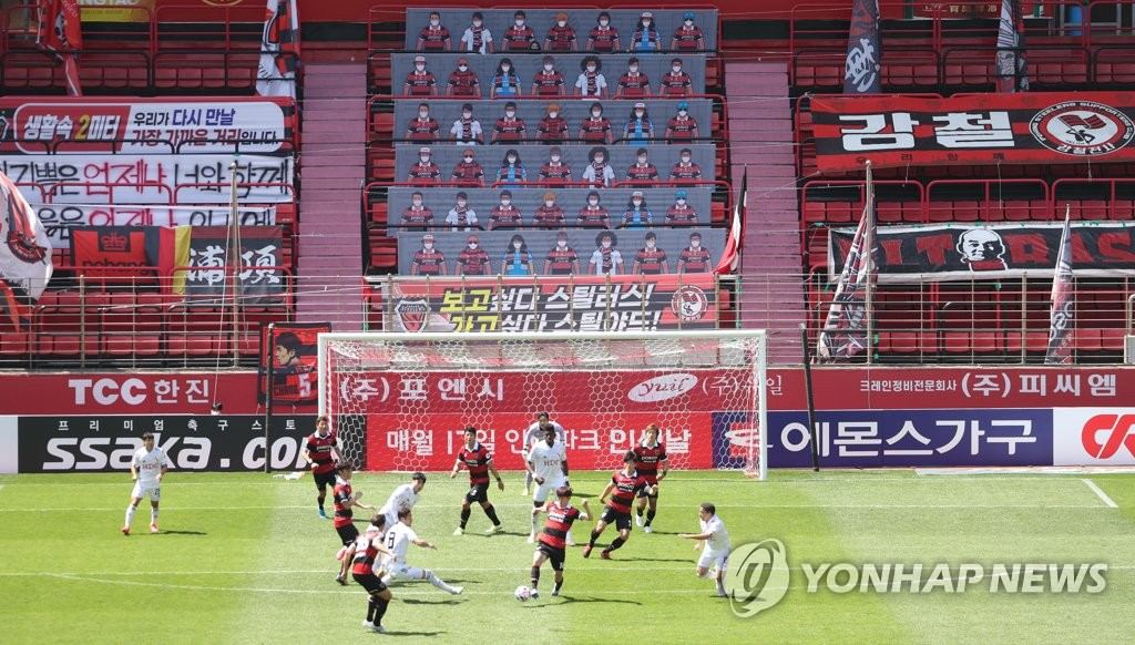 This file photo from May 10, 2020 shows a K League 1 match between Pohang Steelers and Busan IPark being played at an empty Pohang Steel Yard in Pohang, 370 kilometers southeast of Seoul, with banners showing mask-clad fans covering up seats. (Yonhap)