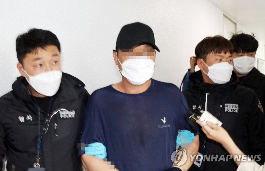 In this photo, taken May 27, 2020, a Chinese man (second from L) is taken to the Taean Coast Guard station in Taean, located some 130 kilometers southwest of Seoul in South Chungcheong Province, for questioning on suspicions of having illegally entered South Korea on a boat. (Yonhap)