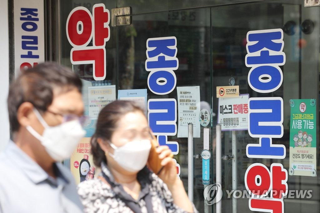 Pedestrians wearing face mask walk past a pharmacy in the central Seoul ward of Jongno on May 31, 2020. (Yonhap)