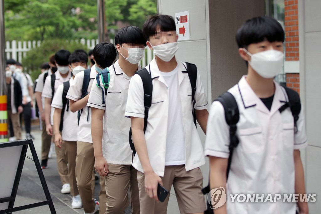 Students stand in a line to have their body temperatures checked before entering their classrooms at a high school in the southwestern city of Gwangju, 329 kilometers south of Seoul, on June 3, 2020. (Yonhap)