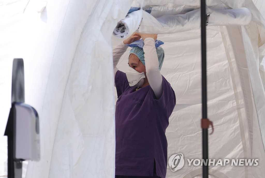 A medical worker cools her head with an ice pack at a makeshift clinic in northern Seoul on June 8, 2020. (Yonhap)