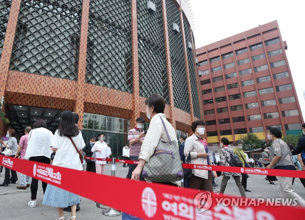 Wearing masks, worshipers line up to enter Yoido Full Gospel Church in Seoul, the biggest Protestant church in South Korea with 560,000 congregants, on June 14, 2020. (Yonhap)
