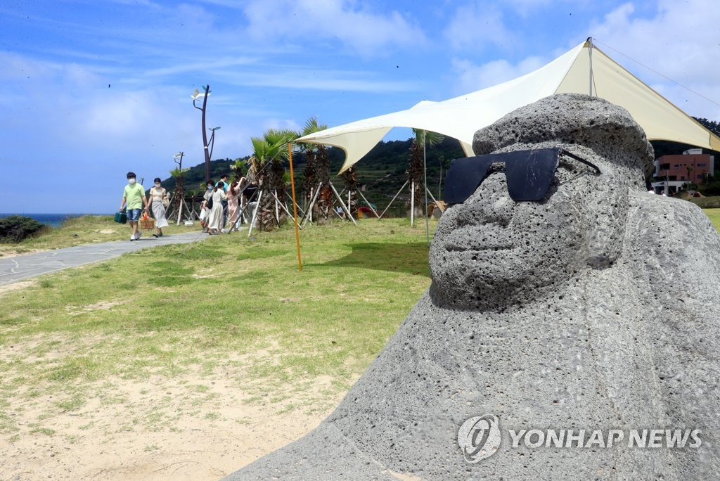 "A ""dolharbang"" (stone grandfather) wears sunglasses at Hamdeok Beach in the city of Jeju on South Korea's southern resort island of Jeju on June 21, 2020. (Yonhap)"