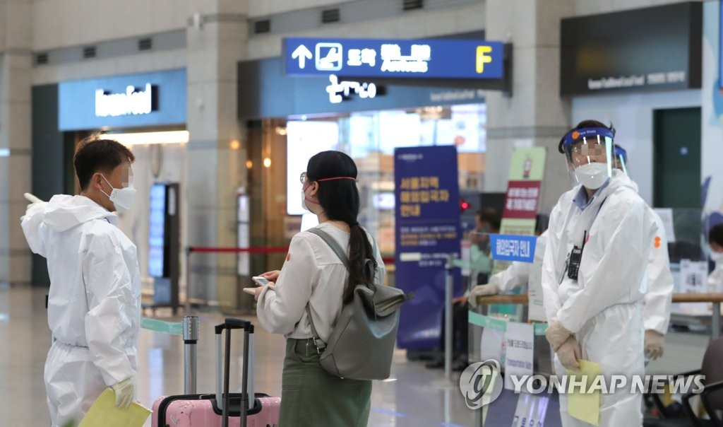 Health workers guide an international arrival through quarantine measures at Incheon International Airport, South Korea's main gateway west of Seoul, on June 23, 2020. (Yonhap)