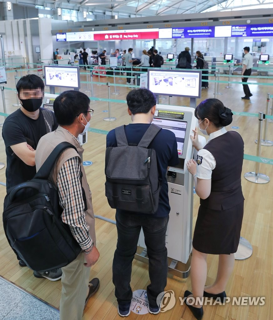 People use an unmanned kiosk to check in before boarding their flights at Incheon International Airport, west of Seoul, on July 1, 2020. (Yonhap)