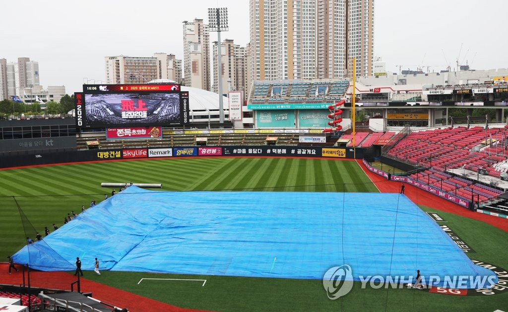 The ground at KT Wiz Park in Suwon, 45 kilometers south of Seoul, is covered with a tarp during a rain delay prior to the Korea Baseball Organization regular season game between the home team KT Wiz and the Samsung Lions on July 12, 2020. The game was cancelled. (Yonhap)