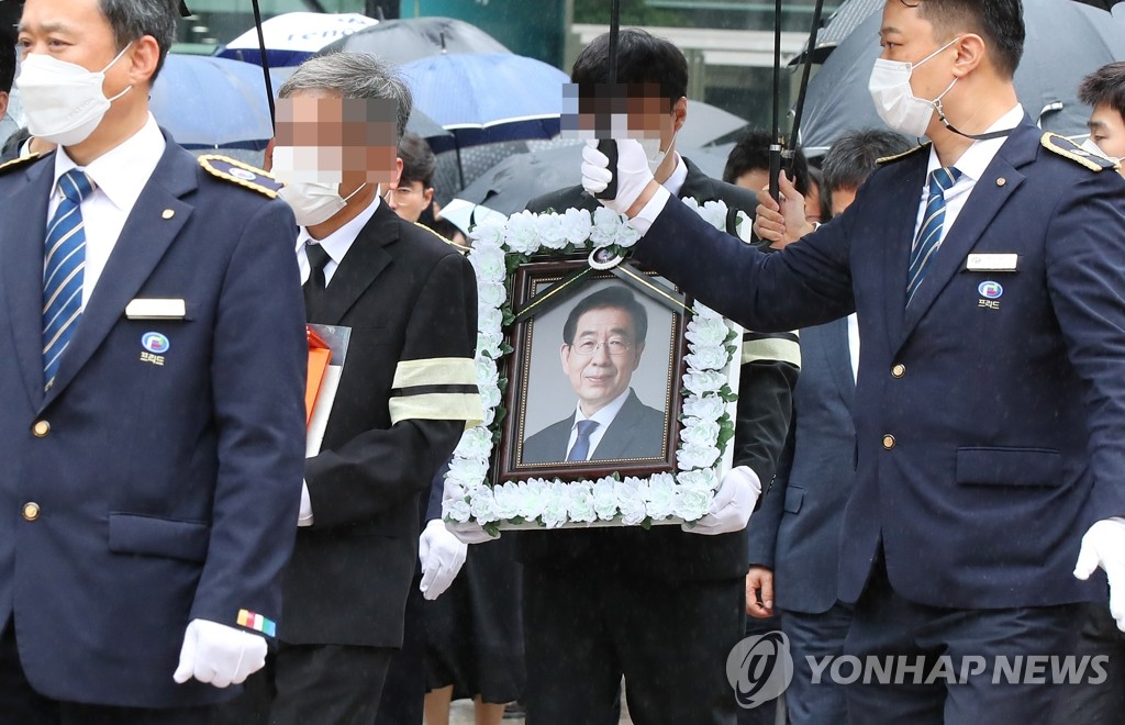 The bereaved family and friends of late Seoul Mayor Park Won-soon carry his photo outside City Hall in central Seoul following a livestreamed funeral on July 13, 2020. (Yonhap)
