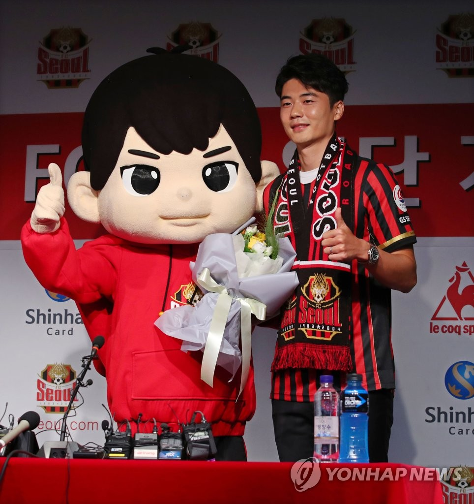 Ki Sung-yueng of FC Seoul (R) poses in his new uniform next to the club mascot at his introductory press conference at Seoul World Cup Stadium in Seoul on July 22, 2020. (Yonhap)