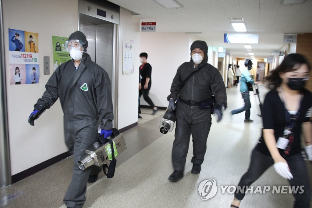 Health workers disinfect the government complex in central Seoul on July 24, 2020, after a family member of an employee at the Personal Information Protection Commission tested positive for the new coronavirus. (Yonhap)