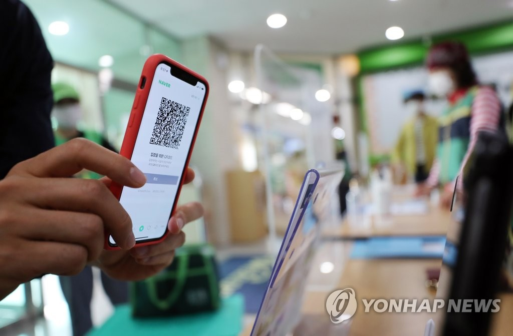 This file photo shows a person using a smartphone to scan a QR code before entering a public building. (Yonhap)