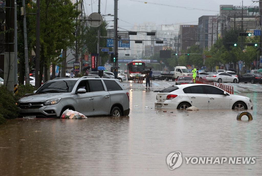 Cars are stranded on a flooded road in the southern city of Gwangju on Aug. 8, 2020. (Yonhap)