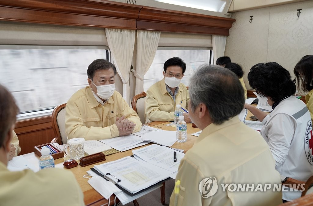 President Moon Jae-in (L, back) receives a briefing on flood damage and recovery work aboard the presidential bullet train on Aug. 12, 2020. (Yonhap)