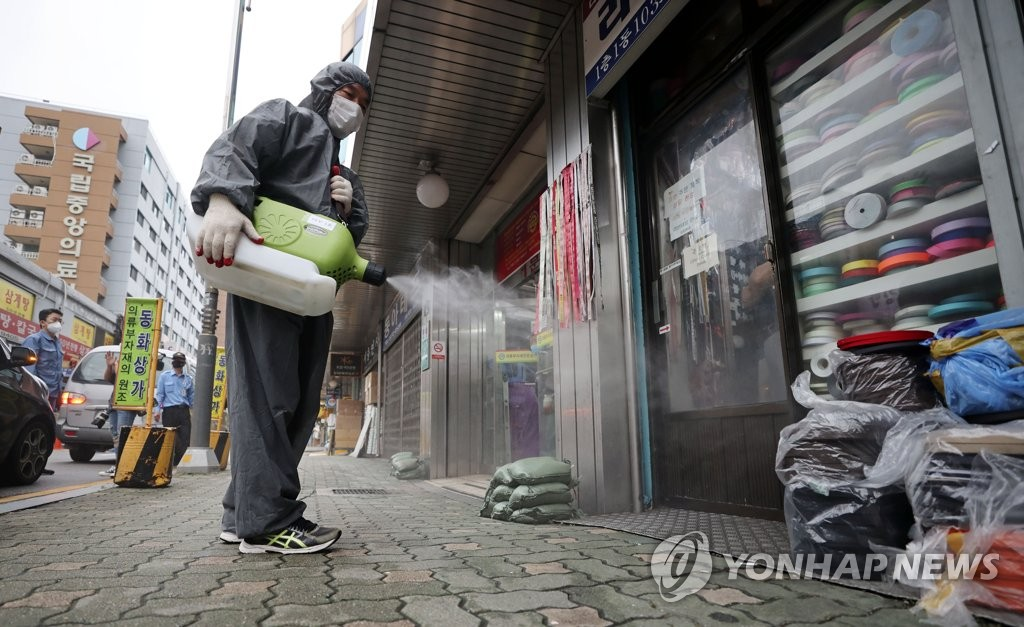 A quarantine official disinfects areas near the Dongwha shopping center in central Seoul on Aug. 14, 2020. (Yonhap)