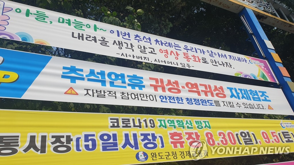 "Signs asking people to refrain from traveling during the Chuseok holiday are on display in Wando, South Jeolla Province, on Sept. 8, 2020. One of the signs reads, ""Sons, daughter-in-laws, we will take care of Chuseok this year. Don't think about coming and let's meet through video call."" (Yonhap)"